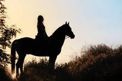 Silueta de una muchacha que monta un caballo en la puesta del sol Foto de archivo libre de regalías