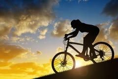 Silueta de una muchacha que monta una bici de montaña Imagen de archivo