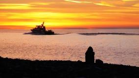 Silueta de una muchacha que se sienta en la playa en el smartphone de la puesta del sol y de las aplicaciones metrajes