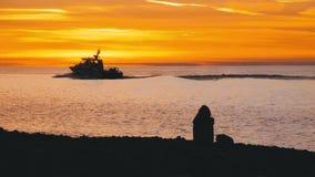 Silueta de una muchacha que se sienta en la playa en el smartphone de la puesta del sol y de las aplicaciones almacen de video
