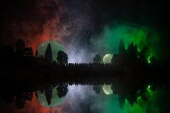 Silueta de una muchedumbre grande de gente en bosque en la noche que mira en la Luna Llena grande de levantamiento Fondo adornado Fotos de archivo