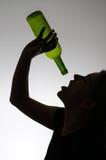 Silueta de una mujer alcohólica con una botella Fotografía de archivo libre de regalías