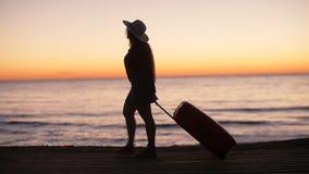 Silueta de una mujer con una maleta en la playa en la puesta del sol almacen de metraje de vídeo
