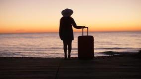 Silueta de una mujer con una maleta en la playa en la puesta del sol metrajes
