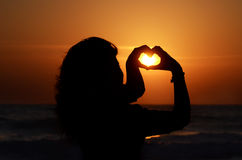 Silueta de una mujer con sus manos que forman un corazón, en la puesta del sol en la playa Foto de archivo libre de regalías