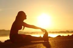 Silueta de una mujer de la aptitud que estira en la puesta del sol Imagen de archivo libre de regalías