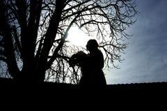 Silueta de una mujer derecha con las flores al lado de un árbol Imagen de archivo