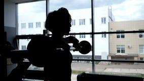Silueta de una mujer en el barbell de elevación de la ventana para los músculos de los hombros metrajes