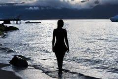 Silueta de una mujer en la playa en la puesta del sol fotos de archivo libres de regalías