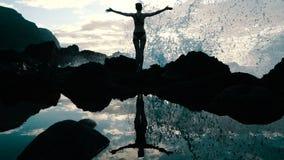 Silueta de una mujer en la puesta del sol que aumenta los brazos en el aire y que observa olas oceánicas enormes el estrellarse e metrajes