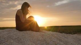 Silueta de una mujer joven en la arena en la puesta del sol, muchacha que ruega a dios en horizonte, el concepto de vacaciones, r metrajes