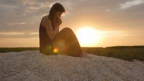 Silueta de una mujer joven en la arena en la puesta del sol, muchacha que ruega a dios en horizonte, el concepto de vacaciones, r almacen de video