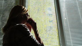 Silueta de una mujer joven por la ventana Él mira la calle a través de las persianas, bebe el café de una taza miradas almacen de video