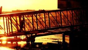 Silueta de una mujer joven que camina en un puente de cristal del jet metrajes