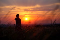 Silueta de una mujer joven que se coloca solamente durante puesta del sol Fotografía de archivo