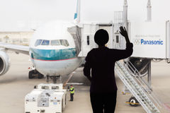 Silueta de una mujer que agita adiós a un aeroplano fotografía de archivo