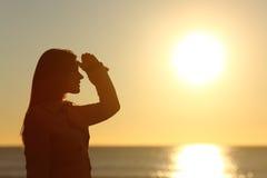 Silueta de una mujer que considera adelante la puesta del sol Imagenes de archivo