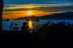 Silueta de una mujer que fotografía la puesta del sol sobre la montaña Foto de archivo libre de regalías
