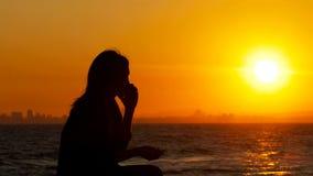 Silueta de una mujer que habla en el teléfono en la puesta del sol
