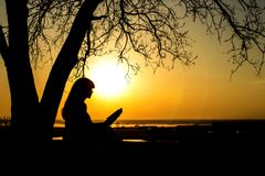 Silueta de una mujer studing la biblia en naturaleza en la puesta del sol, la religión del concepto y la espiritualidad Imagen de archivo