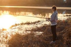 Silueta de una pesca de la chica joven en la puesta del sol cerca del lago foto de archivo