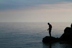 Silueta de una pesca del hombre foto de archivo libre de regalías