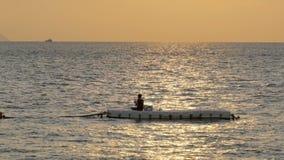 Silueta de una pesca del hombre en el displacer en la puesta del sol Pattaya, Tailandia metrajes