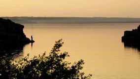 Silueta de una pesca del pescador en el banco del río en la puesta del sol metrajes