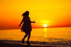 Silueta de una señora que corre por el mar Imágenes de archivo libres de regalías