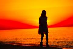 Silueta de una señora que corre por el mar Imagen de archivo
