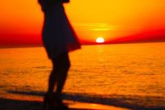 Silueta de una señora y de una salida del sol anaranjada Foto de archivo