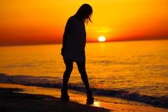 Silueta de una señora y de una salida del sol anaranjada Imagen de archivo