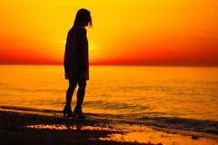 Silueta de una señora y de una salida del sol anaranjada Fotografía de archivo libre de regalías