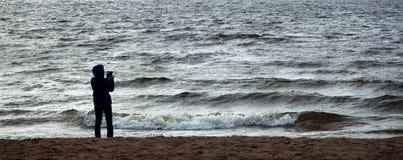 Silueta de una situación de la mujer en la costa y de tomar un phot fotos de archivo