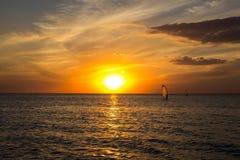 Silueta de una viento-persona que practica surf en puesta del sol de las ondas Fotografía de archivo libre de regalías