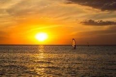 Silueta de una viento-persona que practica surf en puesta del sol de las ondas Imagen de archivo