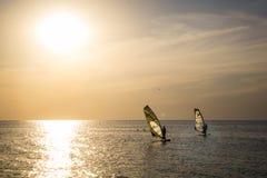 Silueta de una viento-persona que practica surf en puesta del sol de las ondas Foto de archivo libre de regalías