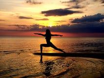 Silueta de una yoga practicante de la muchacha en la playa Tiroteo contra el sol Puesta del sol sobre el mar fotos de archivo libres de regalías
