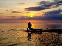 Silueta de una yoga practicante de la muchacha en la playa Tiroteo contra el sol Puesta del sol sobre el mar fotos de archivo
