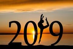 Silueta del Año Nuevo 2019 del baile de la muchacha en la puesta del sol de oro Imágenes de archivo libres de regalías