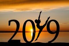 Silueta del Año Nuevo 2019 del baile de la muchacha en la puesta del sol de oro Imagenes de archivo