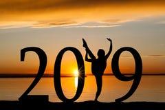 Silueta del Año Nuevo 2019 del baile de la muchacha en la puesta del sol de oro Imagen de archivo libre de regalías