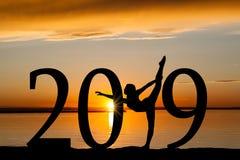 Silueta del Año Nuevo 2019 del baile de la muchacha en la puesta del sol de oro Fotos de archivo