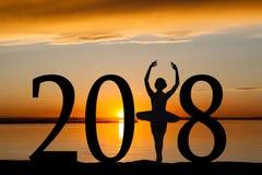 Silueta del Año Nuevo 2018 de la muchacha del ballet en la puesta del sol de oro Foto de archivo