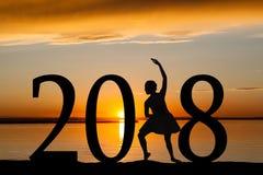 Silueta del Año Nuevo 2018 de la muchacha del ballet en la puesta del sol de oro Fotografía de archivo