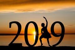 Silueta del Año Nuevo 2019 de la muchacha del ballet en la puesta del sol de oro Imagenes de archivo
