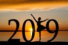 Silueta del Año Nuevo 2019 de la muchacha del ballet en la puesta del sol de oro Imagen de archivo libre de regalías