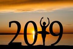Silueta del Año Nuevo 2019 de la muchacha del ballet en la puesta del sol de oro Foto de archivo libre de regalías
