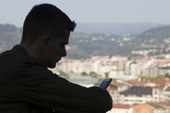 Silueta del adolescente con el teléfono móvil Fotos de archivo libres de regalías
