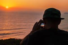 Silueta del adolescente en la puesta del sol del tiroteo del casquillo con su smartphone Imagen de archivo libre de regalías